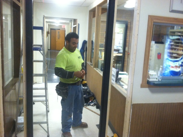 Olmes Medrano, an employee for North Construction, works to install a security door in the hallway that leads to staff offices at Muscatine Center for Social Action.